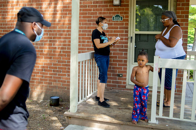 Doyle-Ryder Elementary Principal Daphne Jackson, center, speaks with Flint mother Sharita Watson, 36, on her porch on Monday, Aug. 24, 2020 as Flint Community Schools administrators, support staff and volunteers track down students who have not yet been able to fully connect with their teachers for remote classroom education. (Jake May/The Flint Journal via AP)