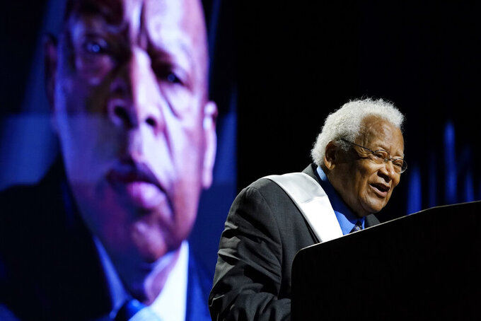 Rev. James Lawson speaks speaks during a celebration of life marking the one-year anniversary of U.S Rep. John Lewis's death Saturday, July 17, 2021, in Nashville, Tenn. A portrait of Rep. Lewis is shown in the background. (AP Photo/Mark Humphrey)