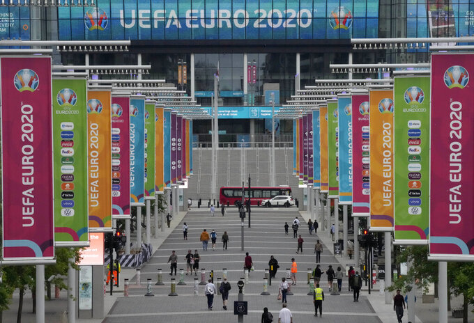 People walk the road to Wembley stadium during the Euro 2020 soccer championship in London, Thursday, June 17, 2021. England is facing Scotland in a group D match on Friday evening at Wembley stadium. (AP Photo/Frank Augstein)