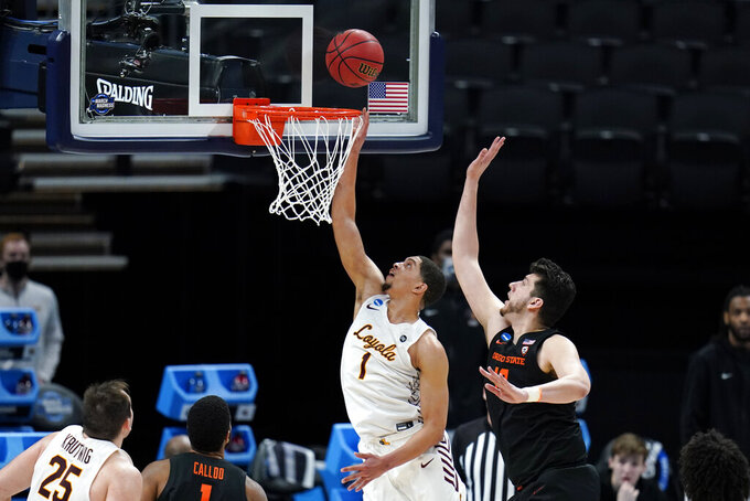 Loyola Chicago guard Lucas Williamson (1) drives to the basket ahead of Oregon State center Roman Silva, right, during the second half of a Sweet 16 game in the NCAA men's college basketball tournament at Bankers Life Fieldhouse, Saturday, March 27, 2021, in Indianapolis. (AP Photo/Jeff Roberson)
