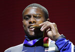 FILE - In this Sept. 29, 2019, file photo, gold medal winner Christian Coleman of the United States, bites on his medal during ceremonies for the men's 100m at the World Athletics Championships in Doha, Qatar. Men's 100-meter world champion Christian Coleman was banned for two years on Tuesday, Oct. 27, 2020, for missing three doping control tests. Track and field's Athletics Integrity Unit said Coleman will be banned until May 2022, forcing him to miss the Tokyo Olympics next year. (AP Photo/Nariman El-Mofty, File)