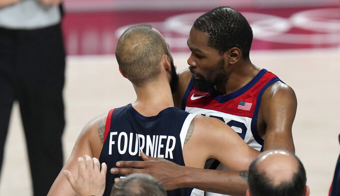 United States' Kevin Durant (7), right, hugs France's Evan Fournier (10) after United States won the men's basketball gold medal game at the 2020 Summer Olympics, Saturday, Aug. 7, 2021, in Saitama, Japan. (AP Photo/Luca Bruno)