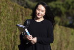 Meng Wanzhou, chief financial officer of Huawei, carries a binder of documents as she leaves her home to attend a hearing at British Columbia Supreme Court, in Vancouver, on Monday, March 22, 2021. (Darryl Dyck/The Canadian Press via AP)