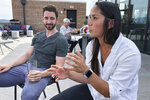 In this June 26, 2019 photo, Marco Teeter and Katherine Schaffer speaks at a rooftop bar at The Bristol Hotel in Bristol, Va. Ten medical students were on a tour of the city organized by a medical school with the aim of luring them to practice in rural communities facing health care shortages after graduation. (AP Photo/Sudhin Thanawala)
