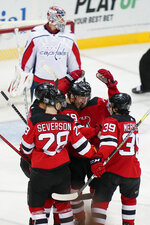 New Jersey Devils' Travis Zajac (19) celebrates with teammates after scoring a goal as Washington Capitals goaltender Ilya Samsonov (30) looks away during the first period of an NHL hockey game Sunday, April 4, 2021, in Newark, N.J. (AP Photo/Frank Franklin II)