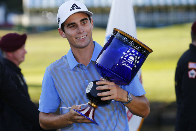FILE - In this Sept. 15, 2019, file photo, Joaquin Niemann holds the winners trophy as he celebrates winning the A Military Tribute at The Greenbrier golf tournament in White Sulphur Springs, W.Va. The West Virginia stop on the PGA Tour has fallen victim to the coronavirus pandemic and a schedule change to the fall. The PGA Tour and The Greenbrier resort announced Thursday, April 16 2020, that A Military Tribute at The Greenbrier, scheduled for Sept. 10-13, has been canceled to make room for other tournaments that had been called off due to the virus. Both parties also announced that the remaining years of the tournament's contract through 2026 have been canceled.(AP Photo/Steve Helber, File)