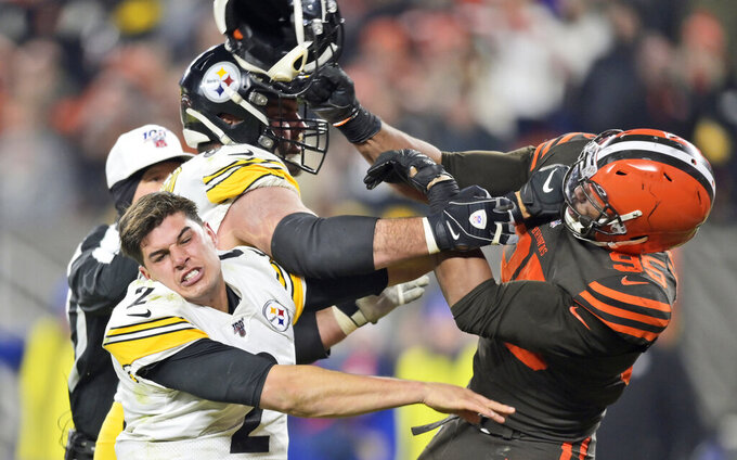 FILE - In this Nov. 14 2019, file photo, Cleveland Browns defensive end Myles Garrett (95) hits Pittsburgh Steelers quarterback Mason Rudolph (2) with a helmet during the second half of an NFL football game in Cleveland. On Sunday, Garrett will face his past and the Steelers for the first time since Nov. 14, when the Browns defensive end let his emotions overpower him and he ripped off the helmet of Pittsburgh's Mason Rudolph and bashed the quarterback over the head. (AP Photo/David Richard, File)