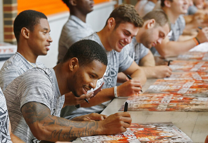 Oklahoma State wide receiver Tyron Johnson, front, signs an autograph as he sits with teammates Jalen McCleskey, left, and Dillon Stoner, right, during the NCAA college football team's fan appreciation day in Stillwater, Okla., Saturday, Aug. 4, 2018. (AP Photo/Sue Ogrocki)