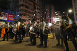 Policemen in riot gear stand on a street as they confront protesters in Hong Kong, Wednesday, Aug. 14, 2019. German Chancellor Angela Merkel is calling for a peaceful solution to the unrest in Hong Kong amid fears China could use force to quell pro-democracy protests. (AP Photo/Vincent Yu)