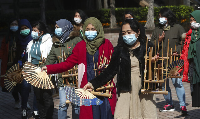 Indonesian migrant workers wear face masks as they play the traditional music instrument