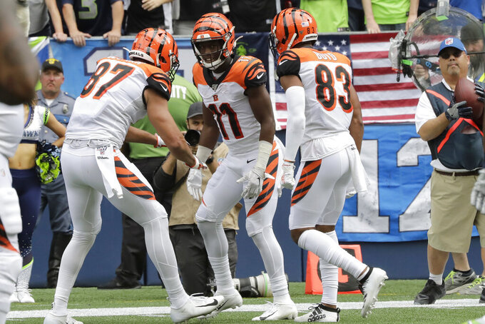 Cincinnati Bengals wide receiver John Ross (11) celebrates with C.J. Uzomah, left, and Tyler Boyd, right, after Ross caught a pass for a touchdown during the first half of an NFL football game against the Seattle Seahawks, Sunday, Sept. 8, 2019, in Seattle. (AP Photo/John Froschauer)