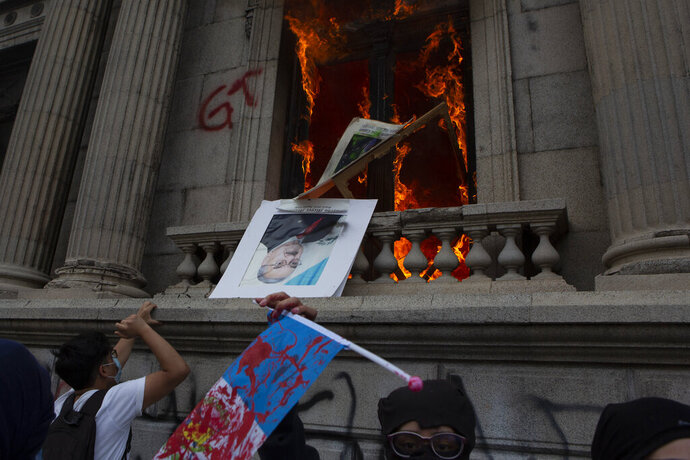 An official photo of former Congress President Eduardo Meyer is thrown out from the Congress building after protesters set a part of the building on fire, in Guatemala City, Saturday, Nov. 21, 2020. Hundreds of protesters were protesting in various parts of the country Saturday against Guatemalan President Alejandro Giammattei and members of Congress for the approval of the 2021 budget that reduced funds for education, health and the fight for human rights. (AP Photo/Oliver De Ros)