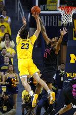Michigan forward Brandon Johns Jr. (23) drives on Penn State forward Lamar Stevens (11) in the first half of an NCAA college basketball game in Ann Arbor, Mich., Wednesday, Jan. 22, 2020. (AP Photo/Paul Sancya)