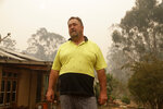 In this Jan, 11, 2020, photo, Joe Seamons stands outside his house at Burragate, Australiaa day after an anticipated wildfire impact failed to come. It seemed imminent to those hunkering at the fire station that