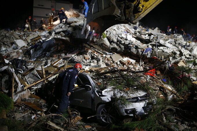 Members of rescue services search a destroyed car amidst the debris of a collapsed building in Izmir, Turkey, early Saturday, Oct. 31, 2020. A strong earthquake struck Friday in the Aegean Sea between the Turkish coast and the Greek island of Samos, killing several people and injuring hundreds amid collapsed buildings and flooding. (AP Photo/Emrah Gurel)