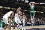 Boston Celtics center Daniel Theis (27) goes up to dunk in front of a group of Indiana Pacers defenders during the second half of an NBA basketball game in Indianapolis, Tuesday, March 10, 2020. The Celtics won 114-111. (AP Photo/AJ Mast)