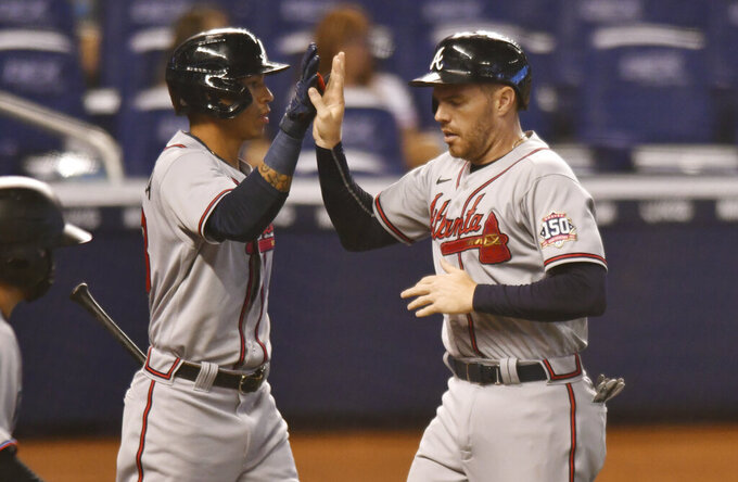 Atlanta Braves' Freddie Freeman, right, is congratulated by teammate Ehire Adrianza after scoring a run in the first inning of a baseball game against the Miami Marlins, Sunday, June 13, 2021, in Miami. (AP Photo/Jim Rassol)