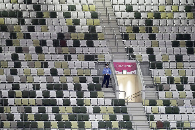 FILE - In this July 23, 2021, file photo, a security officer looks out over an empty stadium before the opening ceremony in the Olympic Stadium at the 2020 Summer Olympics, in Tokyo, Japan. (AP Photo/David J. Phillip, File)
