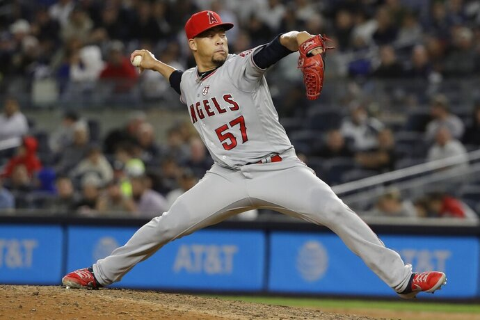 FILE - In this Wednesday, Sept. 18, 2019 file photo, Los Angeles Angels' Hansel Robles throws during the ninth inning of the team's baseball game against the New York Yankees in New York. The Minnesota Twins have signed right-handed reliever Hansel Robles to a $2 million, one-year deal. The Twins announced the signing Tuesday, Dec. 29, 2020. (AP Photo/Frank Franklin II, File)