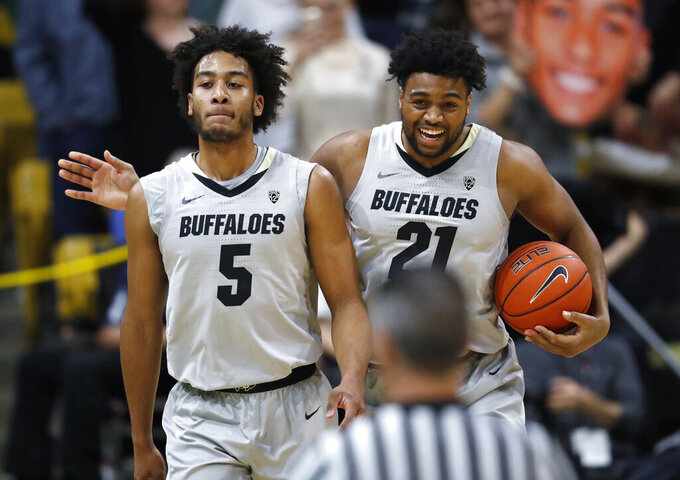 Colorado forward Evan Battey, right, congratulates guard D'Shawn Schwartz after he drew an offensive foul by an Oregon player during the second half of an NCAA basketball game Saturday, Feb. 2, 2019, in Boulder, Colo. Colorado won 73-51. (AP Photo/David Zalubowski)