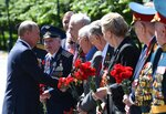 Russian President Vladimir Putin, left, greets WWII veterans during a wreath laying ceremony at the Tomb of Unknown Soldier in Moscow, Russia, Monday, June 22, 2020, marking the 79th anniversary of the Nazi invasion of the Soviet Union. (Alexei Nikolsky, Sputnik, Kremlin Pool Photo via AP)