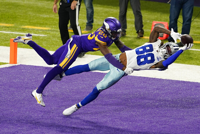 Dallas Cowboys wide receiver CeeDee Lamb catches a 4-yard touchdown pass ahead of Minnesota Vikings cornerback Jeff Gladney, left, during the first half of an NFL football game in Minneapolis on Nov. 22, 2020. (AP Photo/Jim Mone)