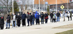First responders, health care workers and law enforcement personnel line up outside of Gillette Stadium in Foxborough, Mass. Thursday, Jan. 21, 2021, to receive their first dose of the Moderna vaccine to combat the coronavirus. Gillette Stadium opened last week as the first mass vaccination site in Massachusetts. (Mark Stockwell/The Sun Chronicle via AP)