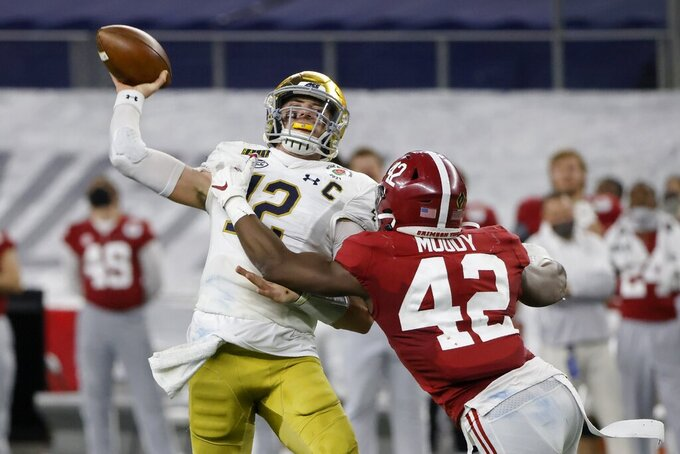 Notre Dame quarterback Ian Book (12) throws an incomplete pass under pressure from Alabama linebacker Jaylen Moody (42) in the second half of the Rose Bowl NCAA college football game in Arlington, Texas, Friday, Jan. 1, 2021. (AP Photo/Michael Ainsworth)