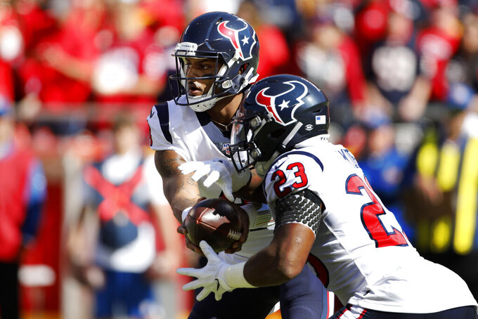 Houston Texans quarterback Deshaun Watson (4) hands the ball off to running back Carlos Hyde (23) during the first half of an NFL football game in Kansas City, Mo., Sunday, Oct. 13, 2019. (AP Photo/Colin E. Braley)