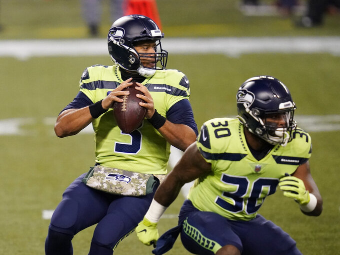 Seattle Seahawks quarterback Russell Wilson looks to pass next to running back Carlos Hyde (30) during the first half of an NFL football game against the Arizona Cardinals, Thursday, Nov. 19, 2020, in Seattle. (AP Photo/Elaine Thompson)