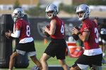 Las Vegas Raiders quarterbacks Marcus Mariota (8), Derek Carr (4) and Nathan Peterman perform drills during an NFL football practice Wednesday, July 28, 2021, in Henderson. (AP Photo/David Becker)