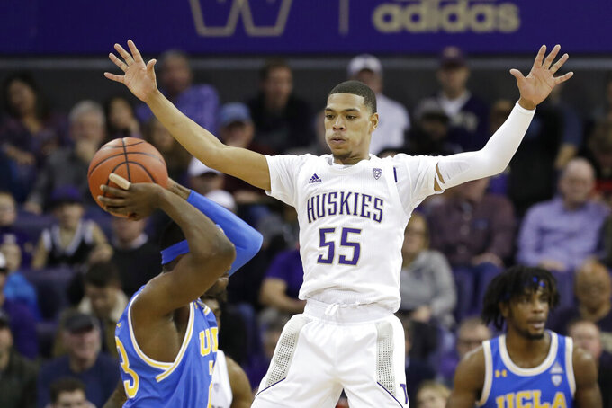 Washington's Quade Green (55) defends against UCLA's Prince Ali in the first half of an NCAA college basketball game Thursday, Jan. 2, 2020, in Seattle. (AP Photo/Elaine Thompson)