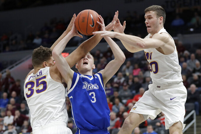 Drake's Garrett Sturtz (3) tries to shoot between Northern Iowa's Noah Carter (35) and Spencer Haldeman during the first half of an NCAA college basketball game in the quarterfinal round of the Missouri Valley Conference men's tournament Friday, March 6, 2020, in St. Louis. (AP Photo/Jeff Roberson)