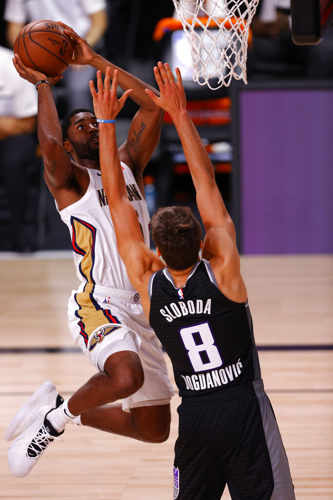 Josh Gray, left, of the New Orleans Pelicans goes up for a dunk against Bogdan Bogdanovic, right, of the Sacramento Kings during the first half of an NBA basketball game Tuesday, Aug. 11, 2020, in Lake Buena Vista, Fla. (Mike Ehrmann/Pool Photo via AP)