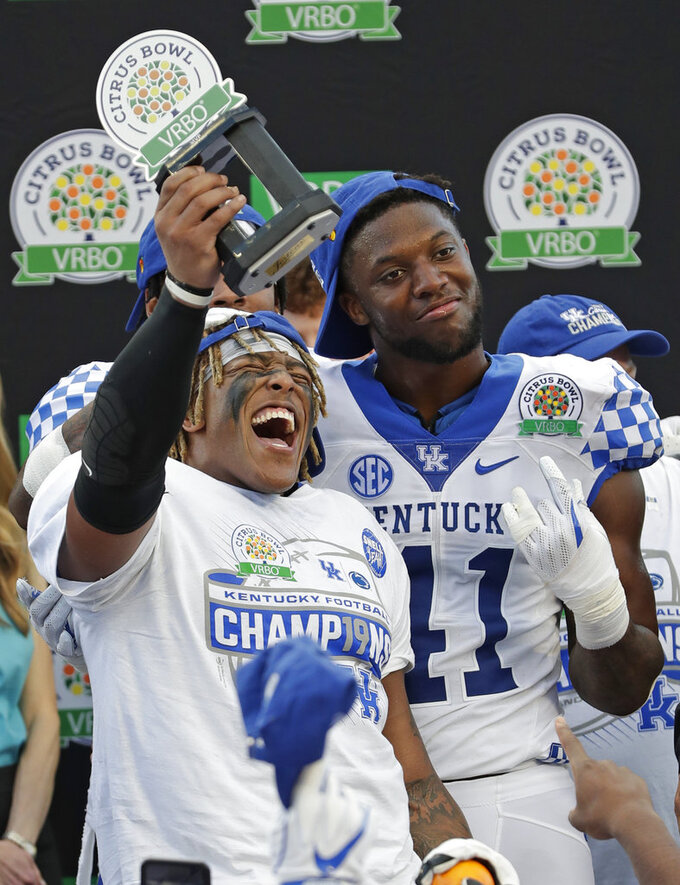 Kentucky running back Benny Snell Jr., left, celebrates holding his MVP trophy with teammate linebacker Josh Allen (41) after defeating Penn State in the Citrus Bowl NCAA college football game, Tuesday, Jan. 1, 2019, in Orlando, Fla. (AP Photo/John Raoux)