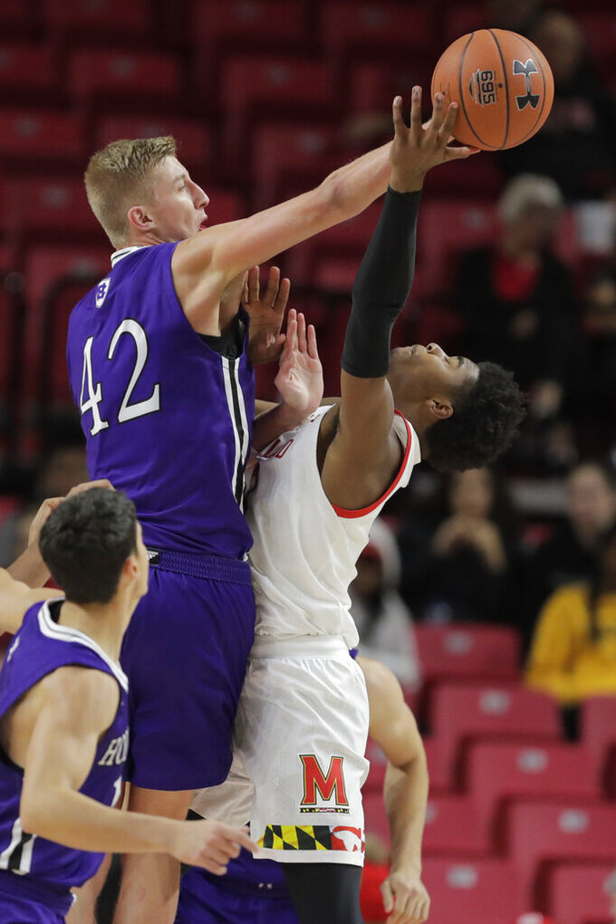 Holy Cross forward Blake Verbeek (42) applies a block on Maryland guard Hakim Hart, right, during the second half of an NCAA college basketball game, Tuesday, Nov. 5, 2019, in College Park, Md. Maryland won 95-71. (AP Photo/Julio Cortez)