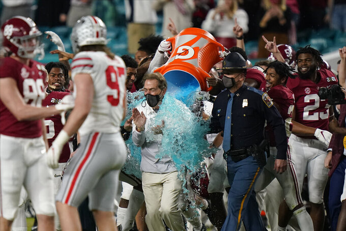 Alabama head coach Nick Saban is soaked in a sports drink after their win against Ohio State in an NCAA College Football Playoff national championship game, Monday, Jan. 11, 2021, in Miami Gardens, Fla. Alabama won 52-24. (AP Photo/Lynne Sladky)