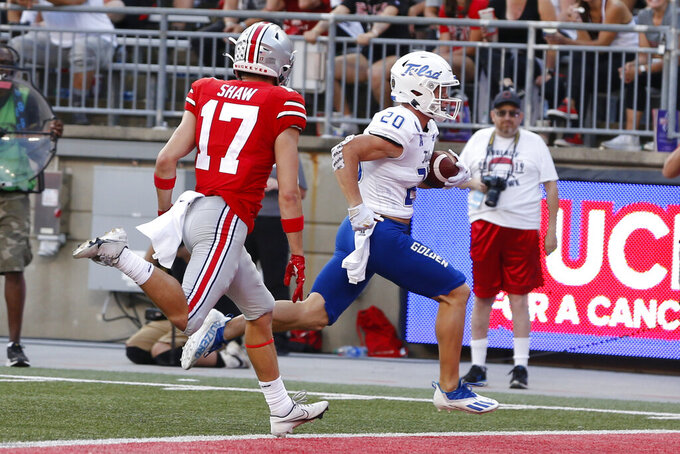 Tulsa receiver Cannon Montgomery, front right, scores a touchdown past Ohio State defensive back Bryson Shaw during the second half of an NCAA college football game Saturday, Sept. 18, 2021, in Columbus, Ohio. (AP Photo/Jay LaPrete)