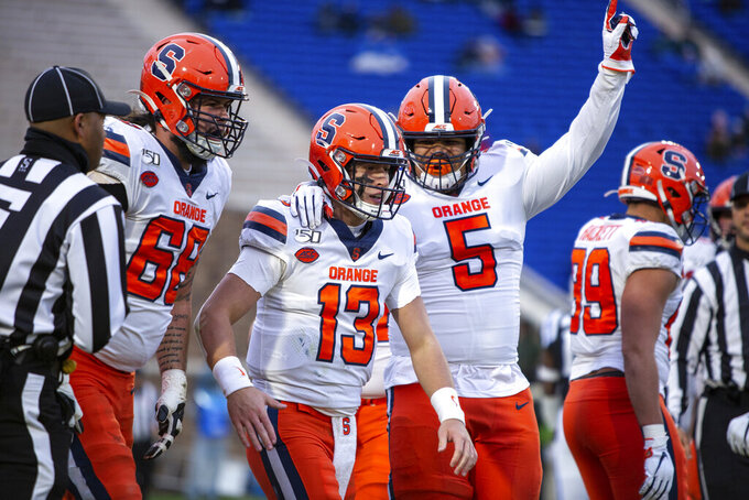 FILE - In this Nov. 16, 2019, file photo, Syracuse's Tommy DeVito (13) celebrates with Chris Elmore (5) and Airon Servais (68) after a play during an NCAA college football game against Duke in Durham, N.C. The Syracuse Orange have missed three practices because of concerns about COVID-19 safety protocols, but the players so far have publicly exhibited a dose of solidarity about playing during the coronavirus pandemic. (AP Photo/Ben McKeown, File)