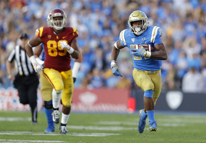 FILE - In this Nov. 17, 2018, file photo, UCLA running back Joshua Kelley, right, runs for a touchdown against Southern California during the second half of an NCAA college football game in Pasadena, Calif. The offense returns nine starters, including sophomore quarterback Dorian Thompson-Robinson and senior running back Joshua Kelley, who went for 289 yards in the victory over USC. (AP Photo/Marcio Jose Sanchez, File)