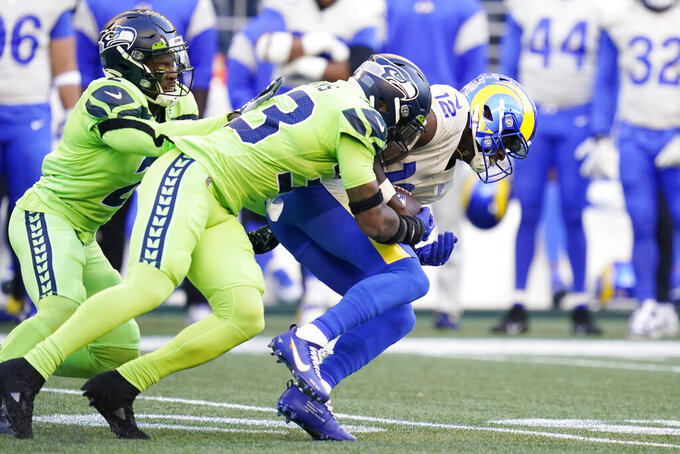 Los Angeles Rams wide receiver Van Jefferson (12) is tackled by Seattle Seahawks safety Jamal Adams (33) and free safety D.J. Reed, left, during the first half of an NFL football game, Thursday, Oct. 7, 2021, in Seattle. (AP Photo/Elaine Thompson)