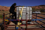 In this April 27, 2020, photo, Chris Topher Chee waits for water to fill a tank in the back of his truck to haul home in Oljato-Monument Valley, Utah, on the Navajo reservation. Even before the pandemic, people living in rural communities and on reservations were among the toughest groups to count in the 2020 census. (AP Photo/Carolyn Kaster)