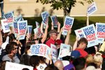 Supporters wave signs before Democratic presidential candidate Elizabeth Warren, D-Mass., speaks at a rally Monday, Aug. 19, 2019, at Macalaster College during a campaign appearance in St. Paul, Minn. (AP Photo/Jim Mone)