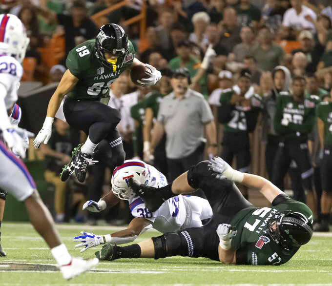 Hawaii wide receiver Jason-Matthew Sharsh (89) jumps over Louisiana Tech safety Darryl Lewis (38) and his teammate offensive lineman J.R. Hensley (57) in the first half of the Hawaii Bowl NCAA college football game, Saturday, Dec. 22, 2018, in Honolulu. (AP Photo/Eugene Tanner)