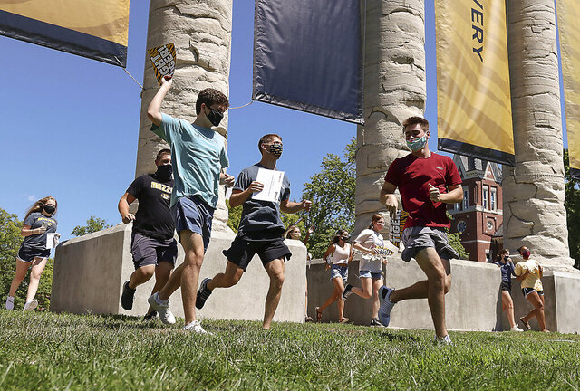Incoming freshmen run through the University of Missouri columns on Aug. 19, 2020, for the Tiger Walk, in Columbia, Mo. As waves of schools and businesses around the country are cleared to reopen, college towns are moving toward renewed shutdowns because of too many parties and too many COVID-19 infections among students. (Owen Ziliak/Missourian via AP)