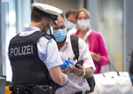 Federal police officers check passengers arriving aboard a flight from Portugal, at Frankfurt airport Tuesday June 29, 2021. As of Tuesday, Portugal is being considered a virus variant area, and people arriving in Germany must go into quarantine. (Boris Roessler/dpa via AP)