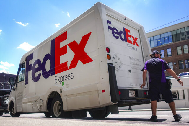 FILE - In this June 25, 2019, file photo, a FedEx delivery truck is loaded by an employee on the street in downtown Cincinnati. FedEx is off to a fast start during the holiday-shipping season. The company said Thursday, Dec. 17, 2020, that its quarterly profit more than doubled to $1.23 billion. Revenue is up 19%, led by growth in its ground business that handles packages. (AP Photo/John Minchillo, File)