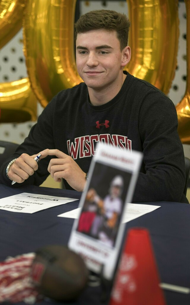 In this Dec. 19, 2019, photo, Graham Mertz acknowledges his intent to play at Wisconsin during a signing ceremony at Blue Valley North High School in Overland Park, Kan. Four scholarship quarterbacks are competing for the starter's job at Wisconsin. When it comes to competing for fans' attention, there's no contest. Freshman Graham Mertz is the Badgers' most hyped recruit in years. (Susan Pfannmuller/The Kansas City Star via AP)