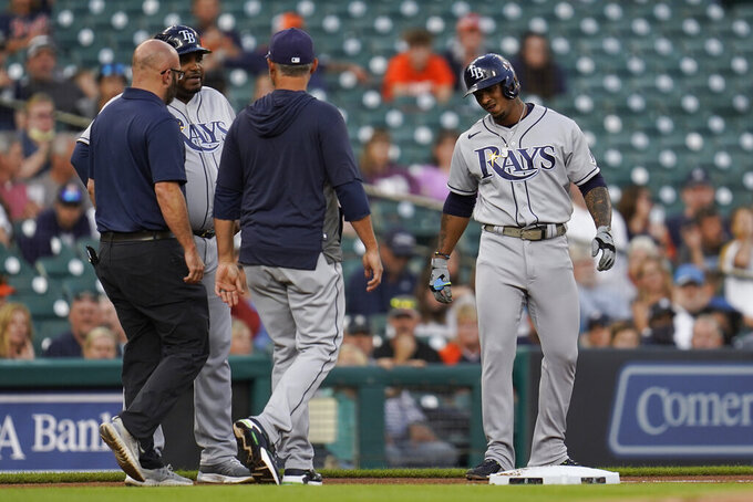Tampa Bay Rays' Wander Franco, from right, grimaces on third base as manager Kevin Cash and a team trainer Joe Benge check on him with third base coach Rodney Linares (27)and against the Detroit Tigers in the first inning of a baseball game in Detroit, Friday, Sept. 10, 2021. Franco left the game. (AP Photo/Paul Sancya)