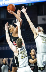 Louisville guard Dre Davis (14) shoots over Wake Forest guard Jonah Antonio (20) and forward Ismael Massoud (25) during an NCAA college basketball game, Wednesday, Jan. 13, 2021 in Winston-Salem, N.C. (Andrew Dye/The Winston-Salem Journal via AP, Pool)